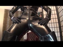Knallenger schwarzer Lackanzug mit hohen Stiefeln